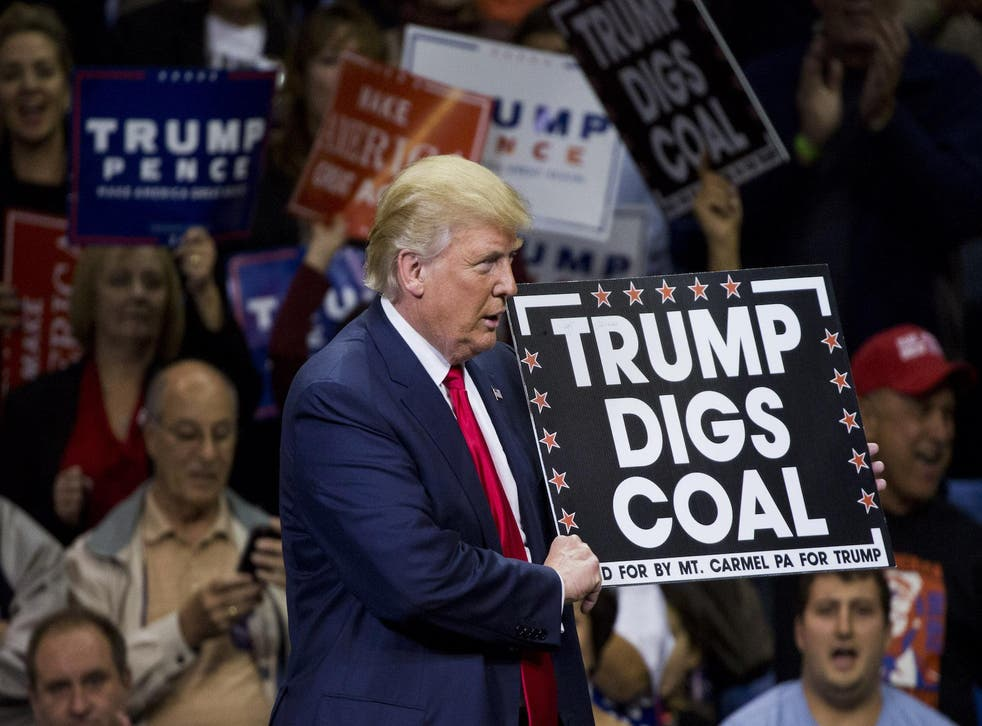 Republican presidential nominee Donald Trump holds a sign supporting coal during a rally at Mohegan Sun Arena in Wilkes-Barre, Pennsylvania on October 10, 2016