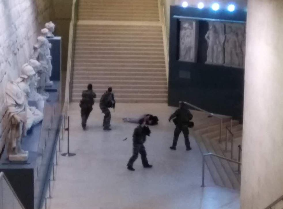 Photo taken by a tourist with a mobile phone shows a soldier opening fire at a man in the Louvre Museum