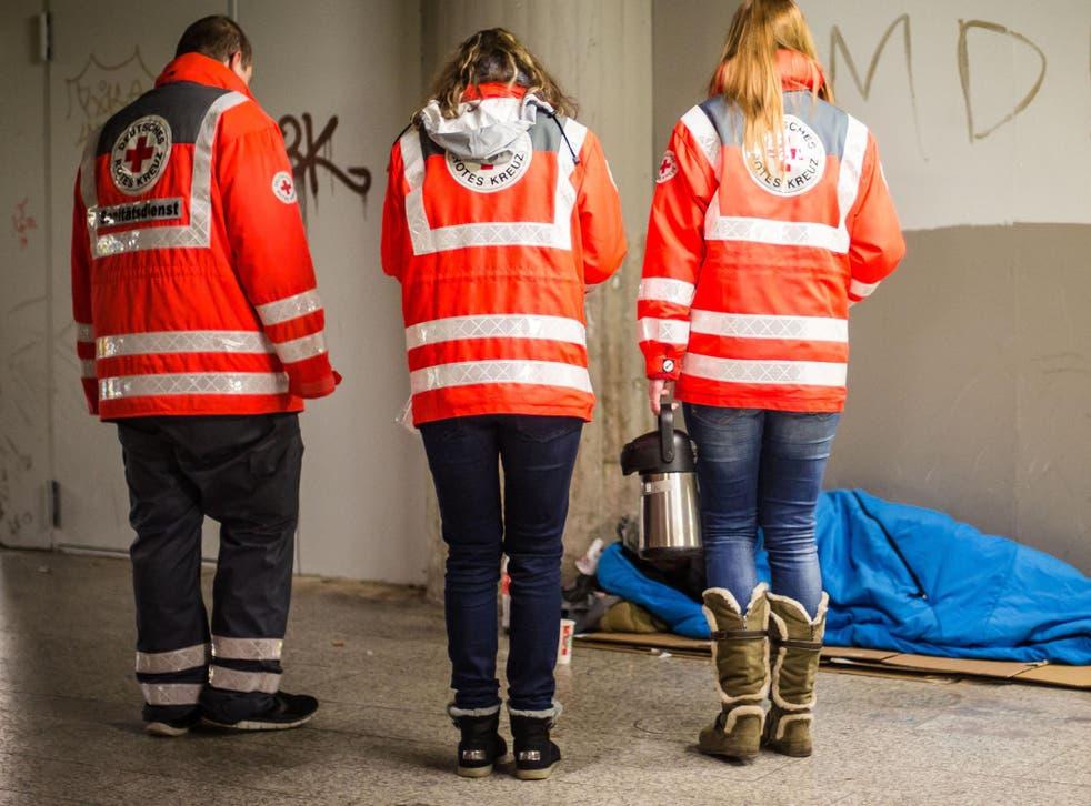 Red Cross volunteers help a homeless man