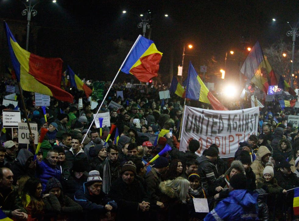 People wave Romanian flags during a protest in front of government headquarters in Bucharest, Romania, on 4 February