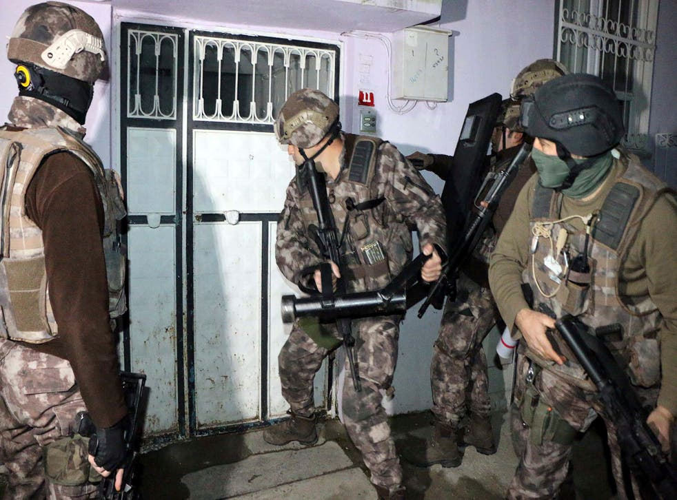 Turkish anti-terrorism police break a door during an operation to arrest people over alleged links to Isis in Adiyaman, southeastern Turkey, during which more than 400  suspects were detained