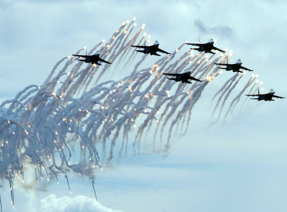 Pilots of the Russian Warriors air force aerobatic squadron fly their Su-27s and fire flares during a demonstration flight at the Moscow International Air Show