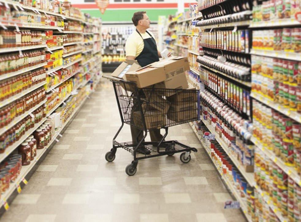 A supermarket worker stocks shelves