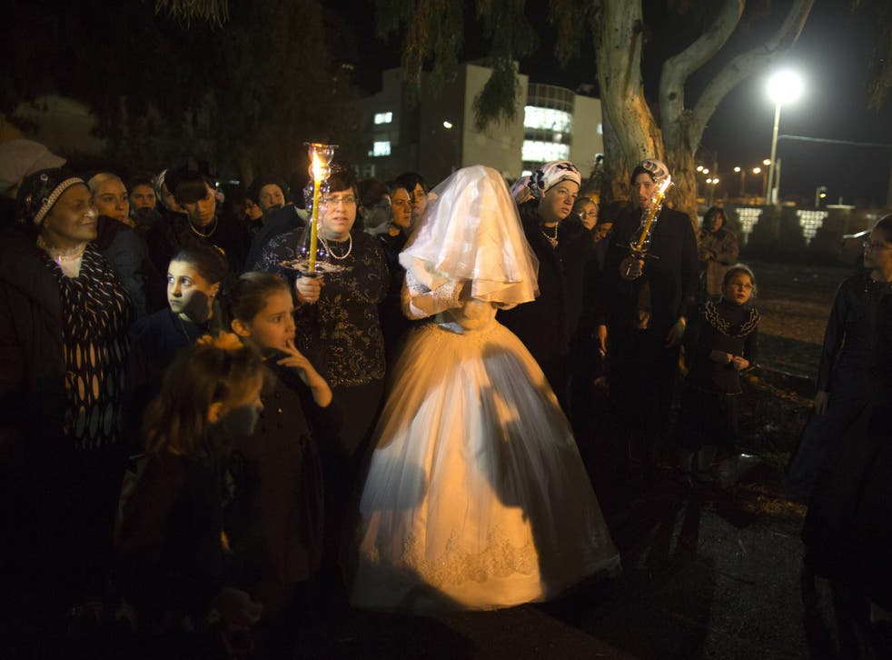 A Jewish woman arrives with family members for her orthodox wedding