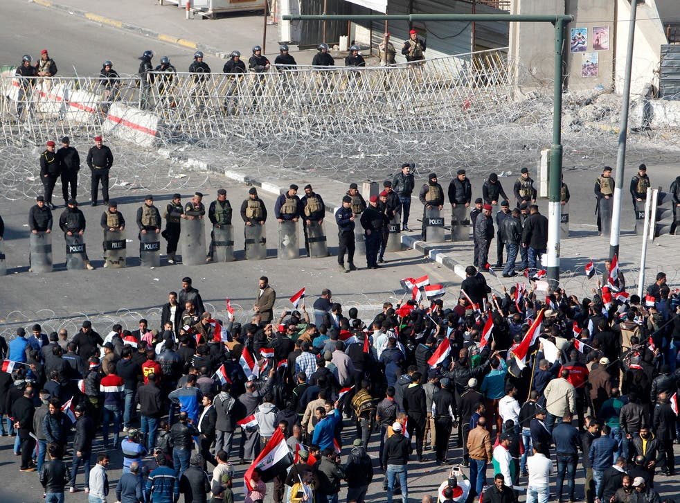 Iraqi security forces stand guard as Sadrist supporters demonstrate in Baghdad's Tahrir Square