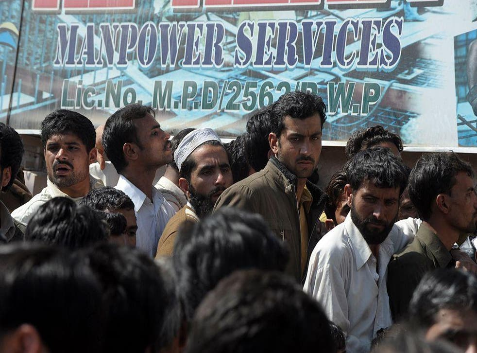 In this file photo Pakistani labourers gather outside the overseas employment consultant office in Rawalpindi on February 23, 2012 to apply for jobs with a construction company in Saudi Arabia