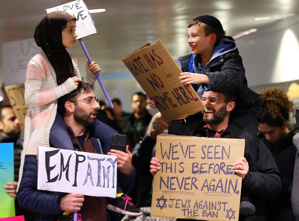 Yildirim, 7, left, sits on her father, Fatih, of Schaumburg, and Adin Bendat-Appell, 9, right, sits on his father, Rabbi Jordan Bendat-Appell, of Deerfield, during a protest at O'Hare International Airport in Chicago