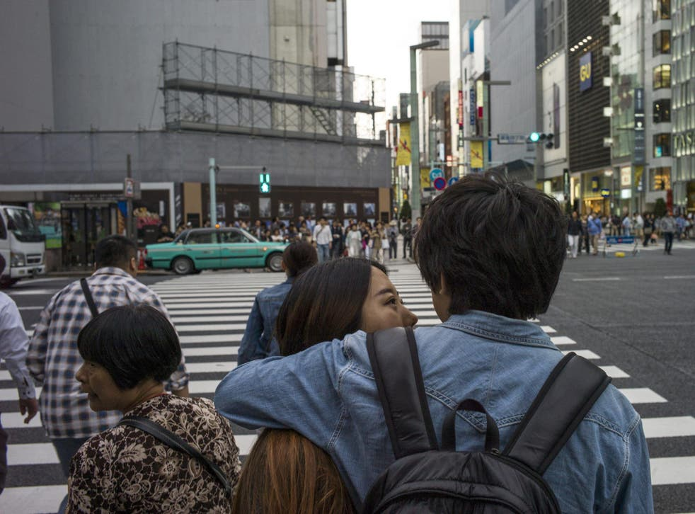 A couple speak at a zebra crossing in Ginza district in Tokyo