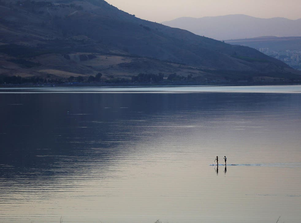 People paddle on a stand-up paddle board in the Sea of Galilee, northern Israel