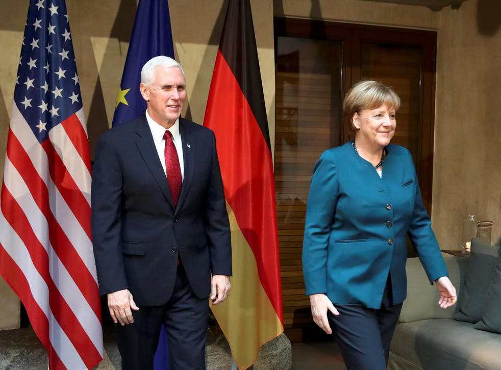 Angela Merkel walks with US Vice President Mike Pence before their meeting at the Munich Security Conference