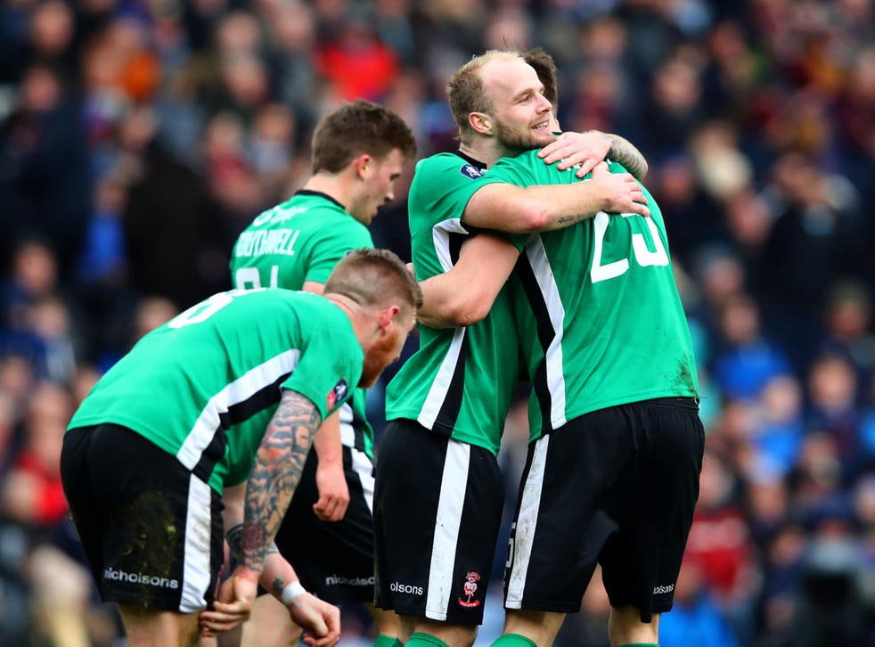 Sean Raggett is mobbed by his team-mates after scoring the winning goal