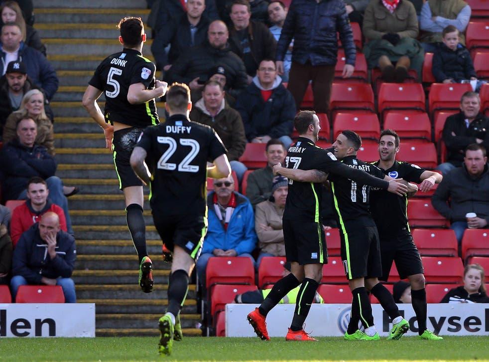 Sam Baldock celebrates with his team-mates after scoring his second for Brighton