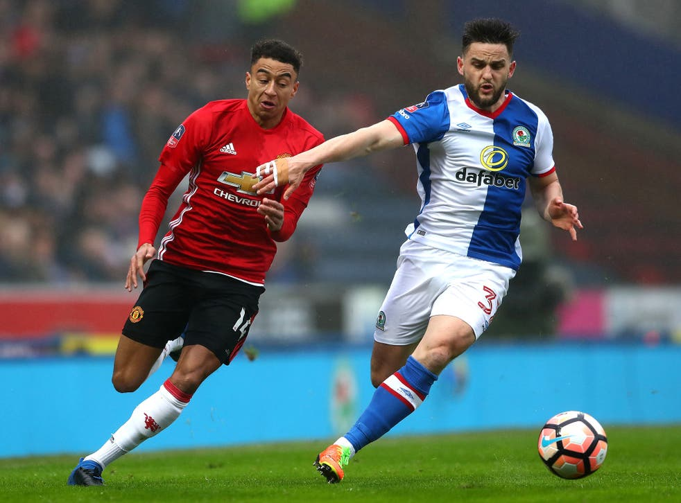 Jesse Lingard and Craig Conway battle for the ball in the opening stages at Ewood Park