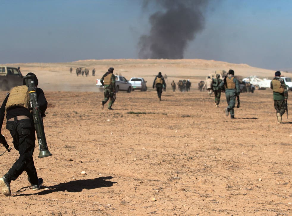 Smoke billows in the background as Iraqi forces, supported by the Hashed al-Shaabi