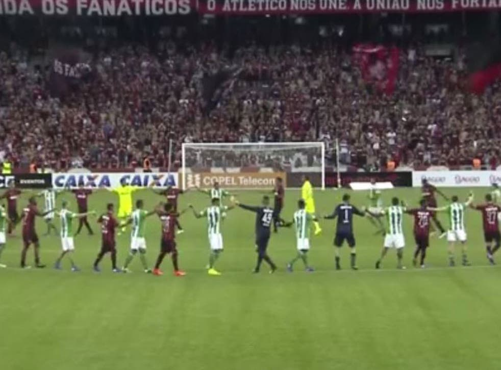 Coritiba and Atletico players salute the crowd as their derby is postponed