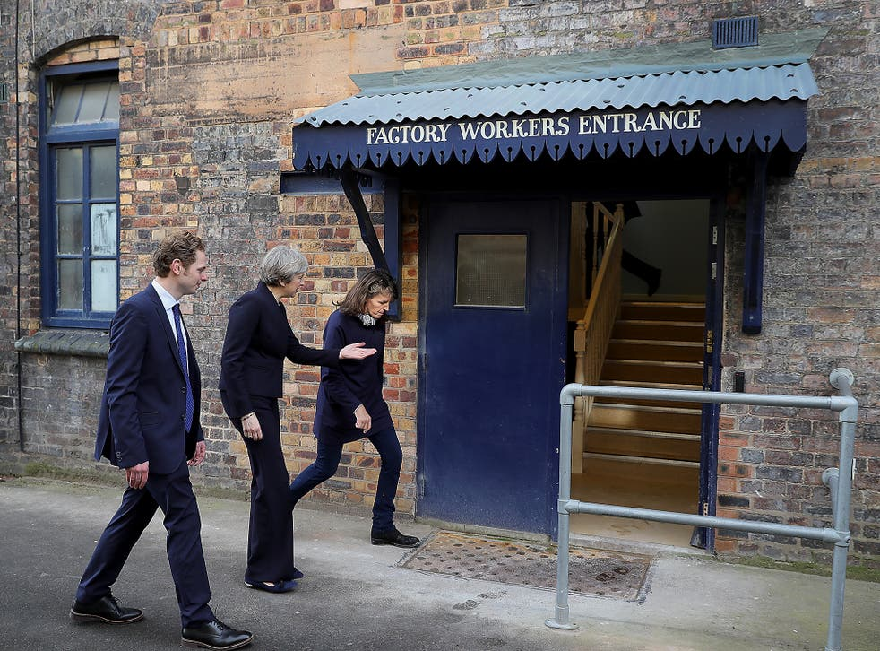 British Prime Minister Theresa May is escorted by Emma Bridgewater and Stoke Central by-election candidate Jack Brereton, as she arrives at the Emma Bridgewater pottery factory in Hanley, Stoke-On-Trent, England