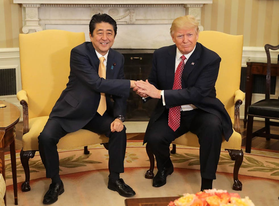 Patting down: the Donald held Japanese PM Shinzo Abe's hand for a gruelling 19 seconds