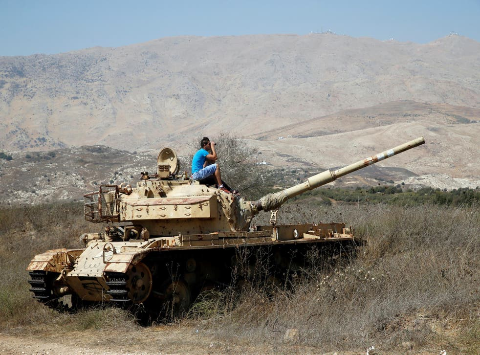 A man sits on an old tank as he watches fighting taking place in Syria as seen from the Israeli side of the border fence between Syria and the Israeli-occupied Golan Heights on September 11, 2