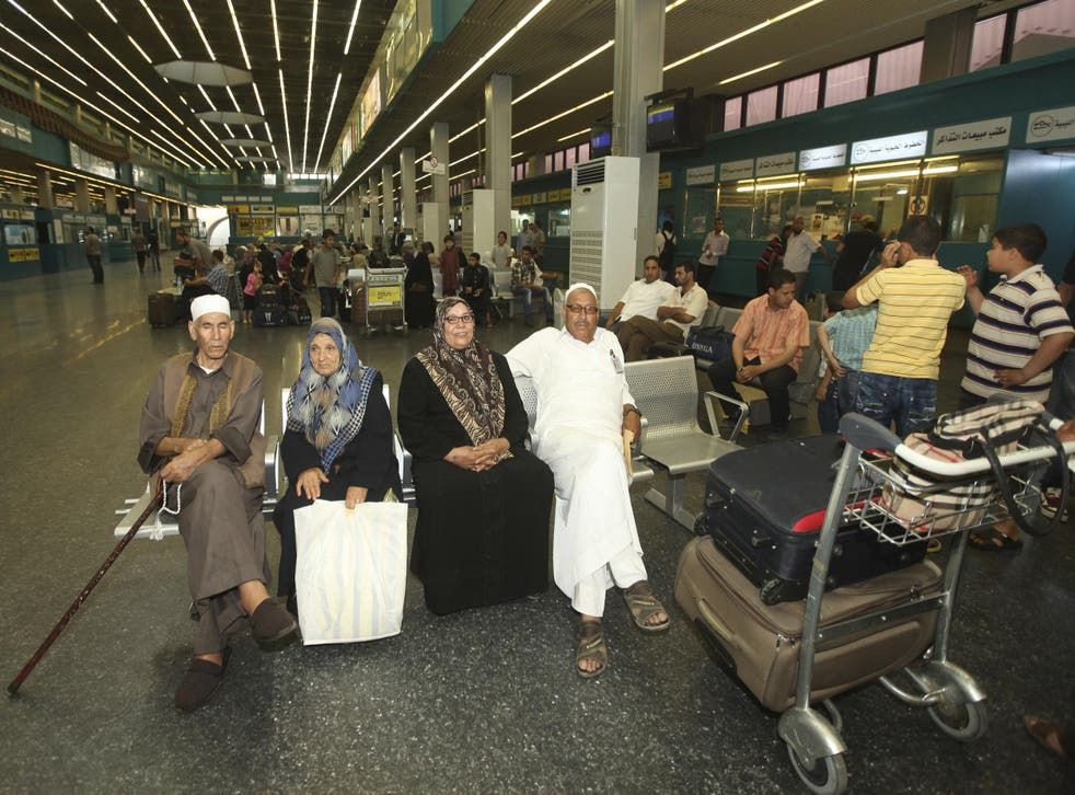 Passengers wait for flights in a hall at Tripoli International Airport on June 5, 2012.