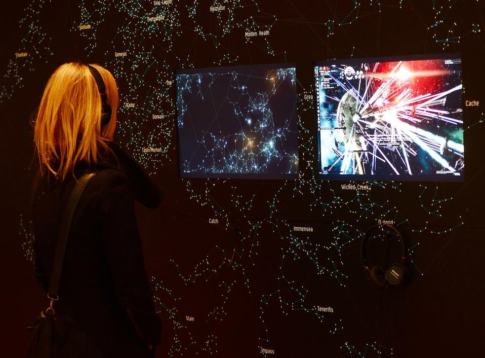 A visitor looks at a demonstration of the video game EVE Online (2003) during an exhibition preview featuring 14 video games acquired by The Museum of Modern Art (MoMA) in New York, March 1, 2013