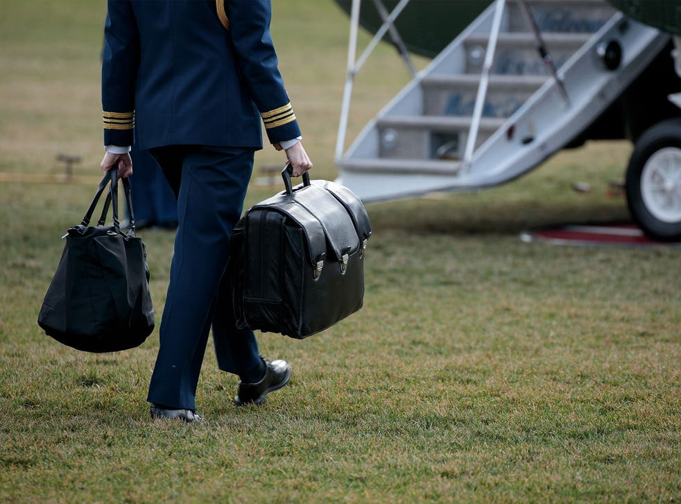 A military aide carries the alleged 'football,' a case with the launch codes for nuclear weapons, toward Marine One as US President Donald Trump prepares to take off on the South Lawn of the White House