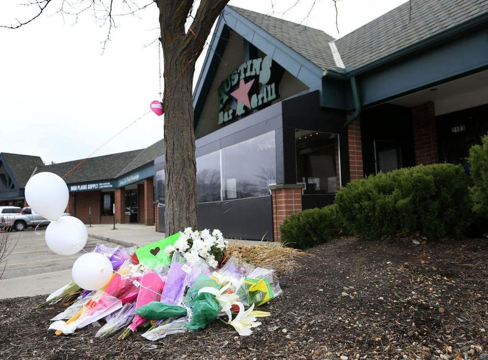 Flowers lie outside the bar where a gunman reportedly asked two Indian men about their visa status before shooting them