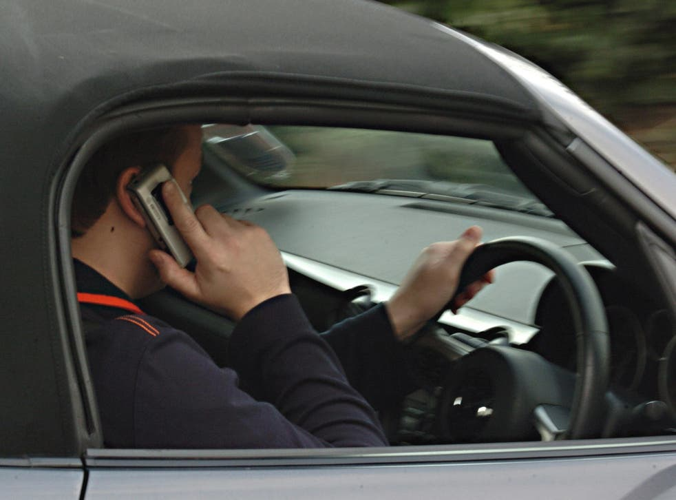 File photo of a man using his mobile phone while driving