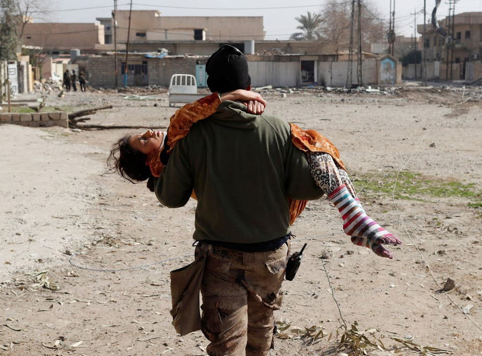 An Iraqi soldier carries a woman injured during a battle between Iraqi forces and Isis fighters in Mosul today