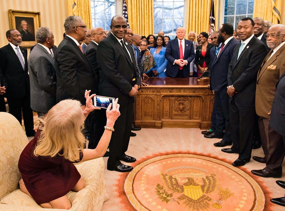 Counselor to the President Kellyanne Conway takes a photo as US President Donald Trump and leaders of historically black universities and colleges talk before a group photo in the Oval Office of the White House