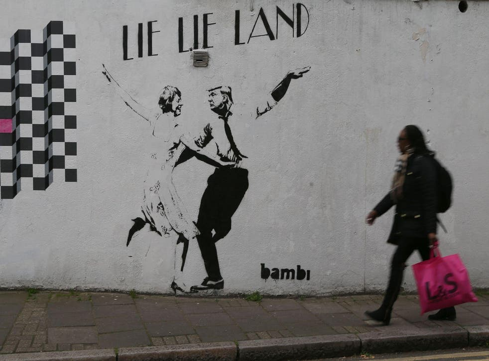 A woman walks past a mural by English street artist Bambi depicting British Prime Minister Theresa May dancing with US President Donald Trump in London on February 22, 2017