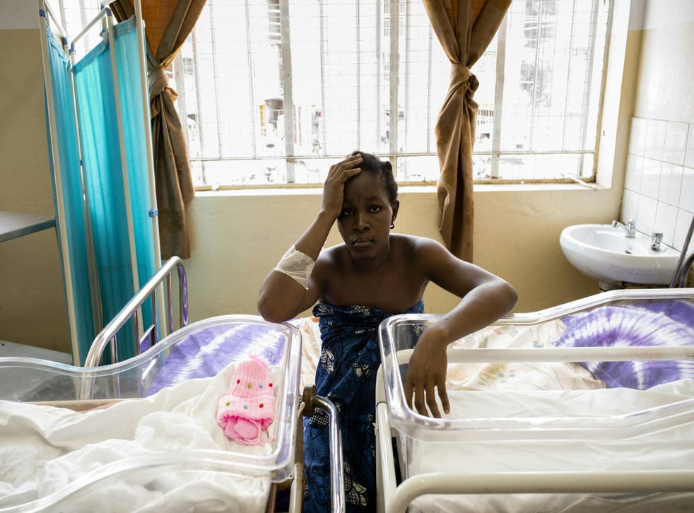 A young mother of twins waits for her children to receive vaccinations in Freetown, Sierra Leone, which has the highest maternal mortality rate in the world