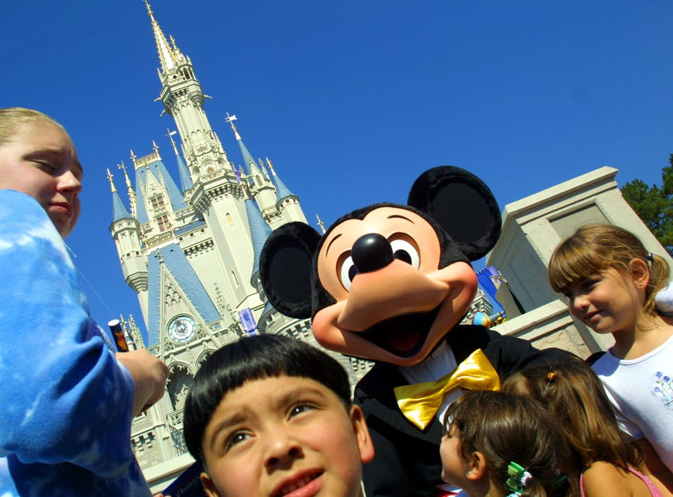Mickey Mouse greets children in front of Cinderella's Castle at Magic Kingdom in  Florida - one of the US destinations that has seen a significant drop in flight searches
