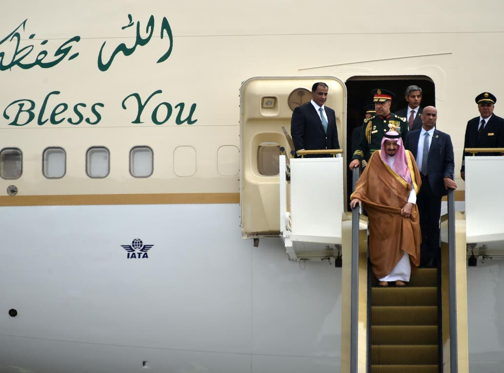 King Salman descends on one of his golden escalators from a plane