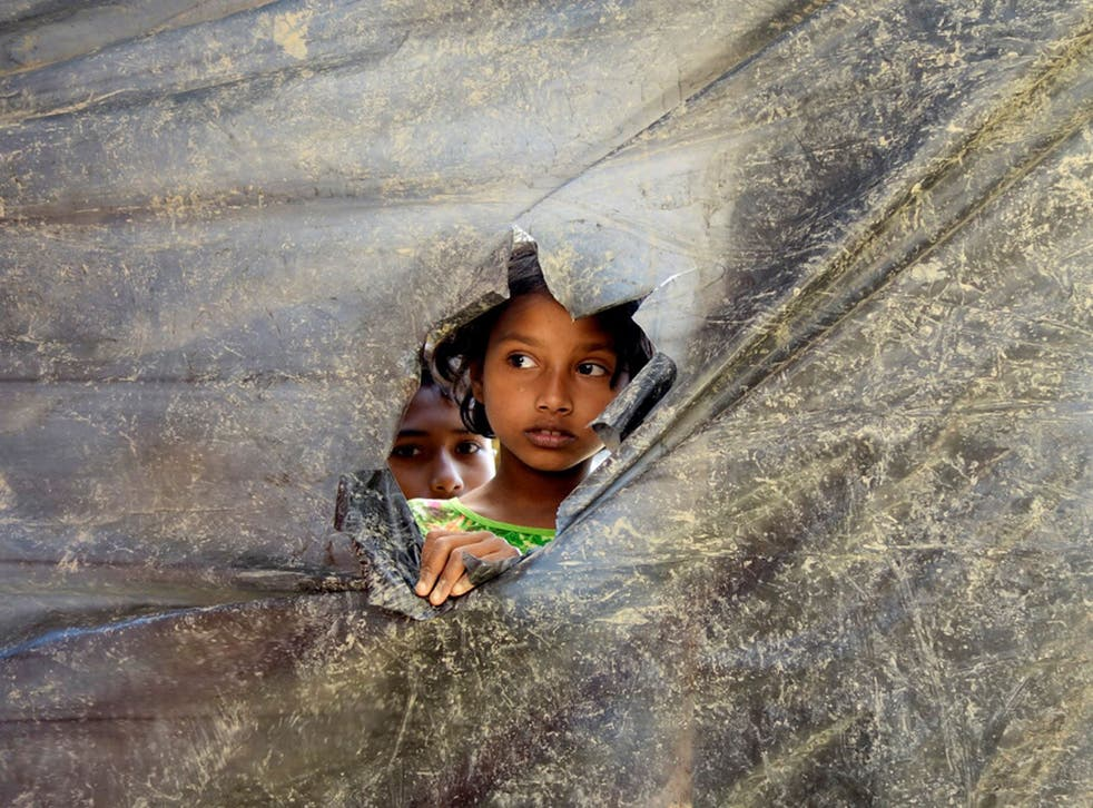 A Rohingya refugee girl peeks through a hole made in a plastic wall dividing the shelters at Balu Kali Refugee Camp in Cox's Bazar, Bangladesh, 28 February, 2017