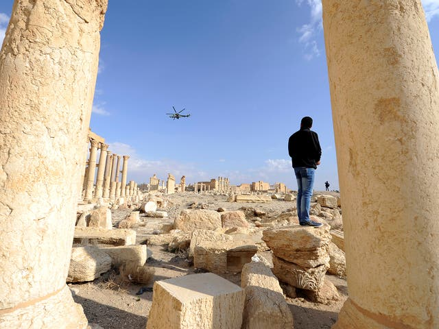 A Russian helicopter flies over ruins in the historic city of Palmyra
