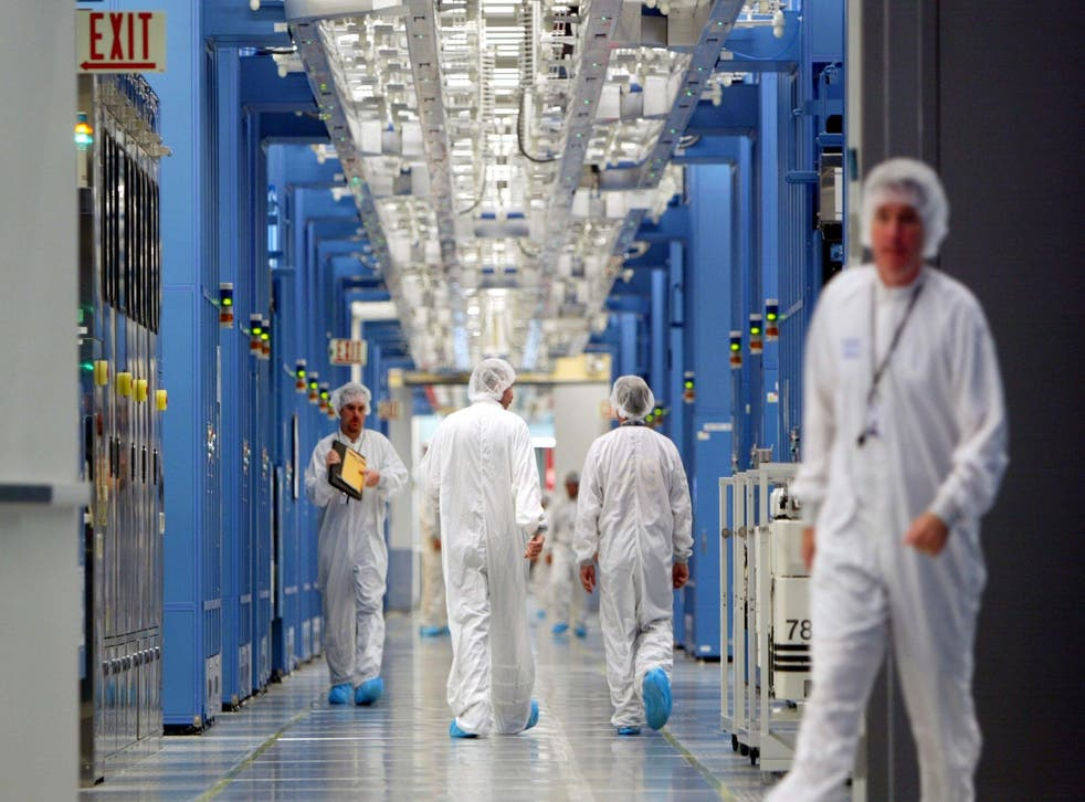 IBM workers walk in an IBM 12-inch wafer chip fabricating plant July 20, 2004 in Fishkill, New York