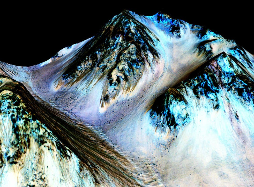 Dark, narrow streaks on the slopes of Hale Crater are believed to have been formed by seasonal flow of water on the surface of Mars
