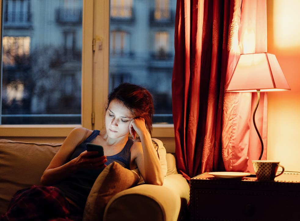 Unhappy woman at home text messaging