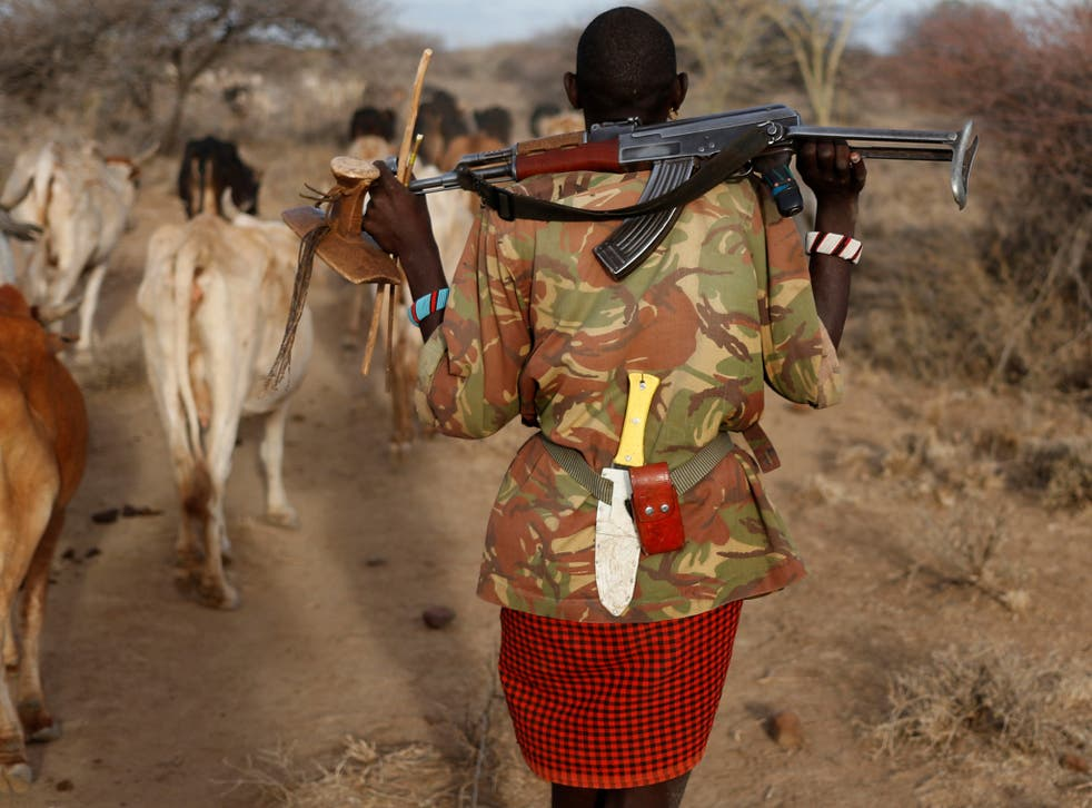 A Turkana tribesman carries a gun in order to protect his cattle as illegal grazing rises in areas hit by drought