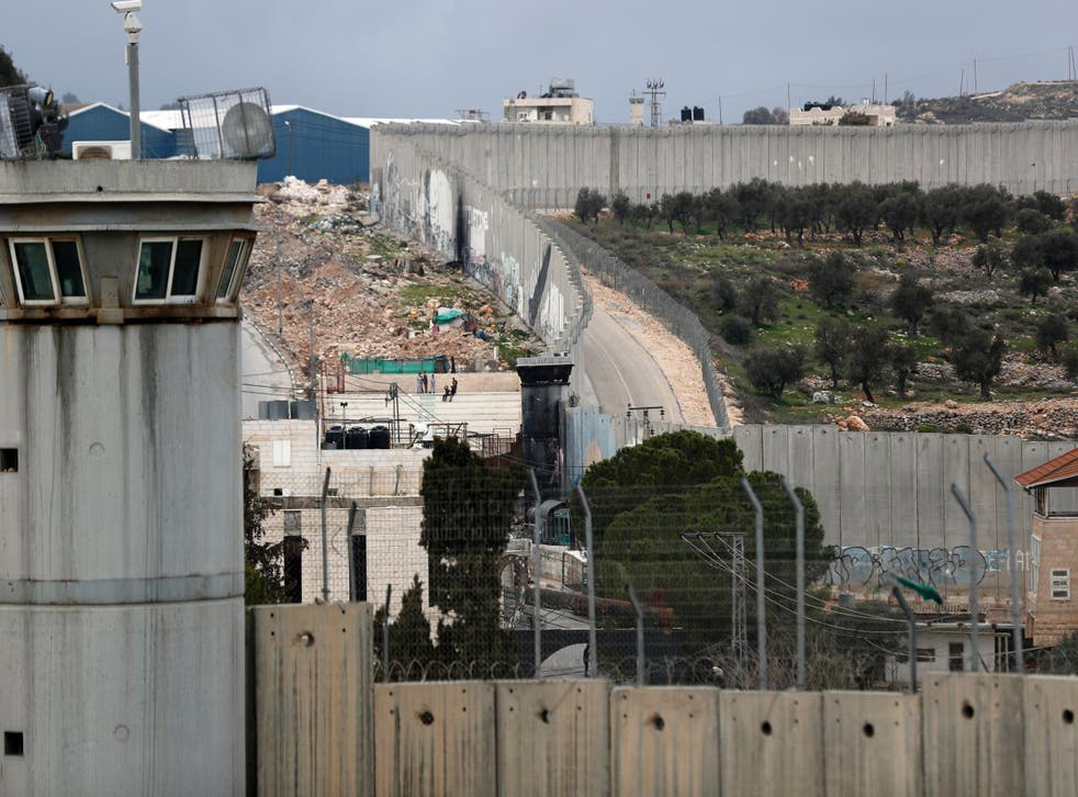 Israel's separation wall as seen from a room in Banksy's Walled Off Hotel which one Palestinian graffiti artist says is turning the grim reality of occupation into a 'Disneyland'