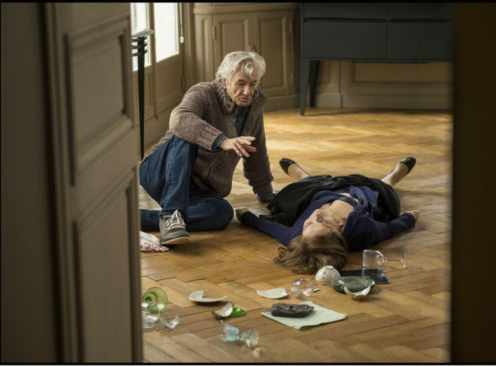 Isabelle Huppert (Michéle) lying on the floor receiving instruction from director Paul Verhoeven in 'Elle'
