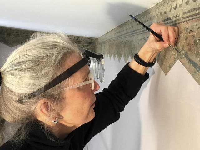 Restoration expert Margaret Saliske works on hand-painted borders at the home of artist Thomas Cole, in Catskill, New York