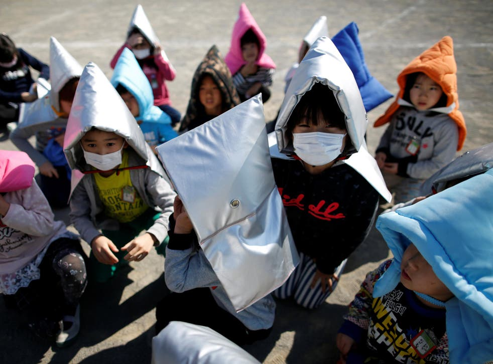 School children wearing padded hoods to protect them from falling debris take part in an earthquake simulation exercise in an annual evacuation drill at an elementary school in Tokyo