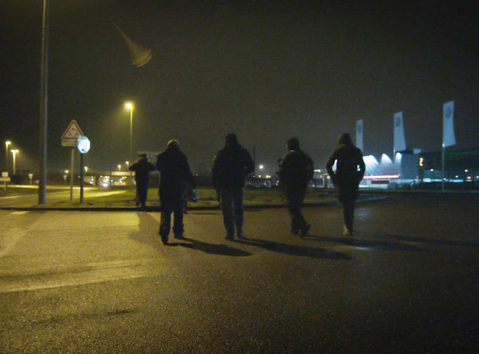 Unaccompanied minors walking in Calais during the night attempting to find a place to try climb aboard lorries without being intimidated by potential people traffickers