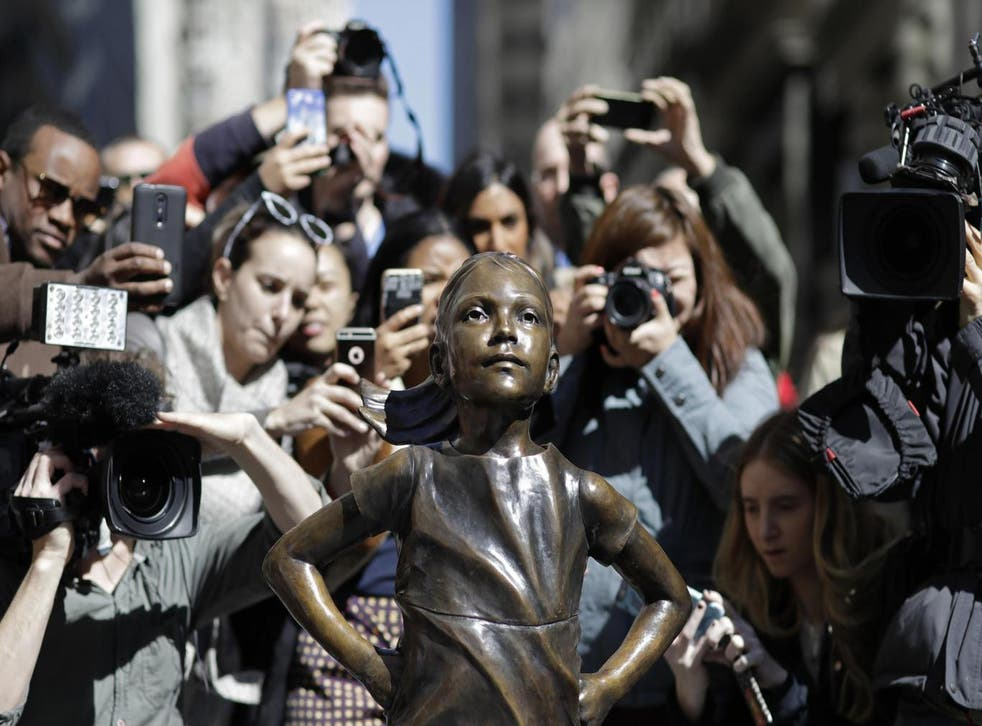 Statue of girl on Wall Street stands opposite a raging bull and is intended to highlight the challenges women face in the financial world