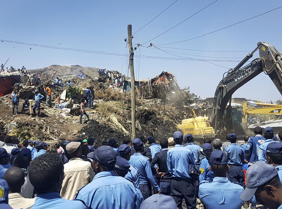 Police officers secure the perimeter at the scene of a garbage landslide, as excavators aid rescue efforts, on the outskirts of the capital Addis Ababa, Ethiopia Sunday, March 12, 2017