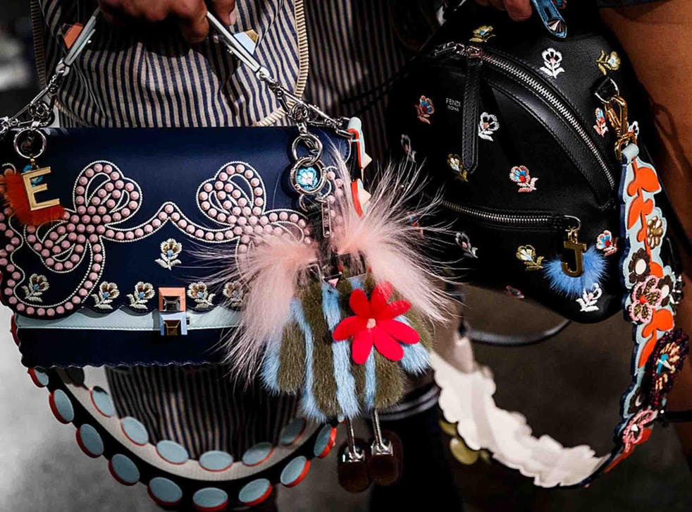 At Fendi, little frame bags were decorated with a clutter of key fobs and furry pom poms
