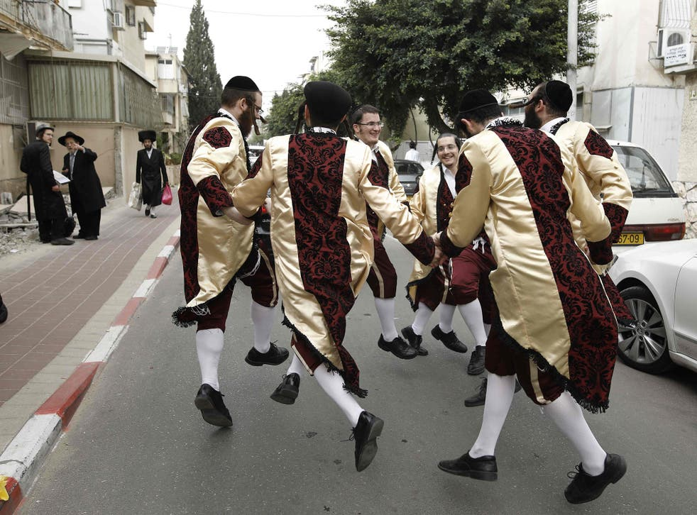 Ultra-Orthodox Jewish men wearing costumes dance on a street in the central Israeli city of Bnei Brak