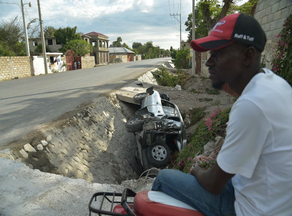 A car damaged by a bus lies on the side of a road yesterday in Gonaives, 150 km (90 miles) northwest of the capital Port-au-Prince