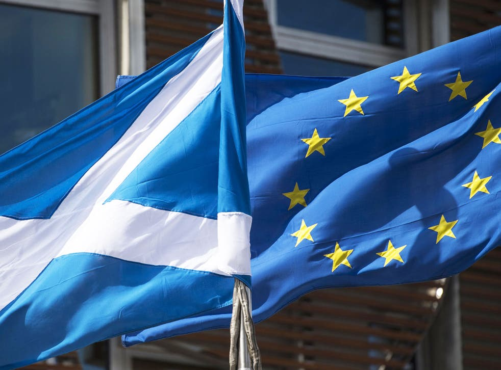 A Scottish Saltire and a European Union flag fly in front of the Scottish Parliament building in Edinburgh